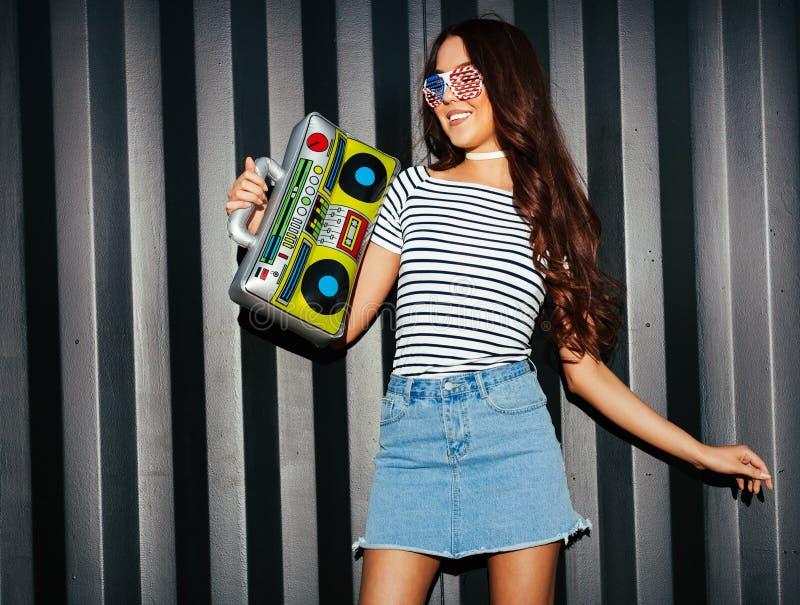 迷人的亚洲女孩看看在牛仔布裙子、T恤杉和美国太阳镜的照相机享受与葡萄酒的音乐 免版税库存照片