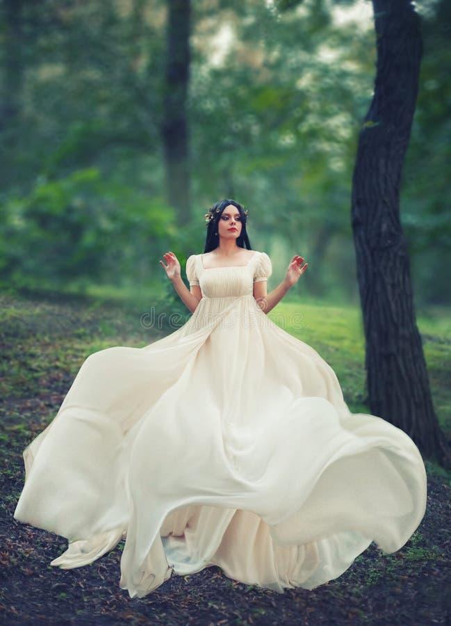 迷人的公主在鲜绿色的森林单独跳舞,长的白色典雅的柔和的礼服的深色头发的女孩有飞行的 免版税库存照片