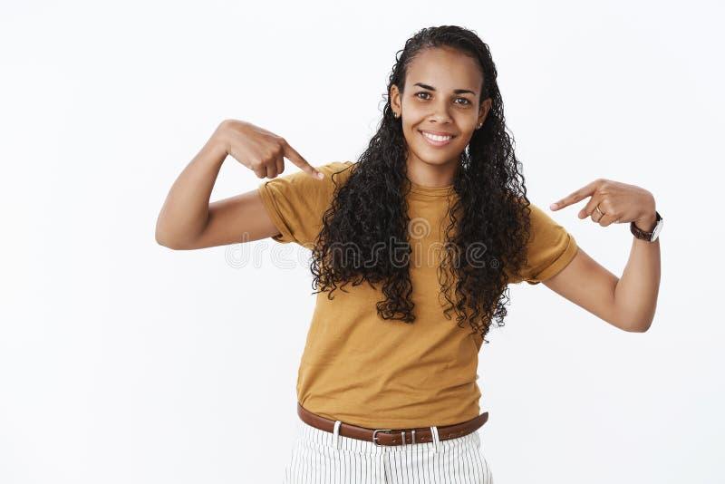 迷人的友好种类和怯懦的非裔美国人的女性妇女有弯曲作为指向的卷曲长发的在 免版税库存照片