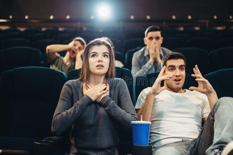 迷人的夫妇观看在戏院的影片 免版税库存照片