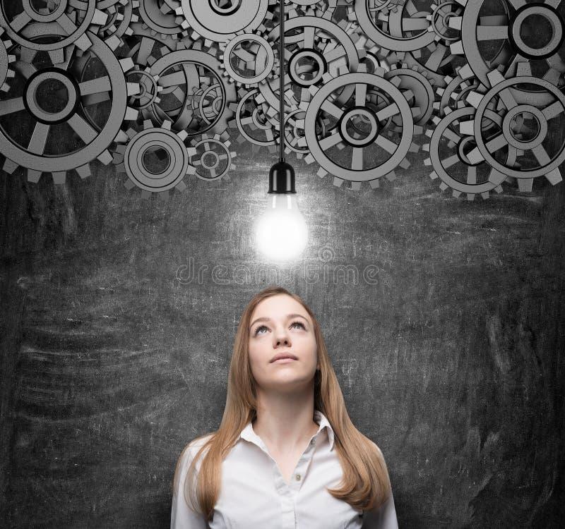 年轻迷人的女商人看电灯泡作为创新企业想法的概念 免版税库存照片