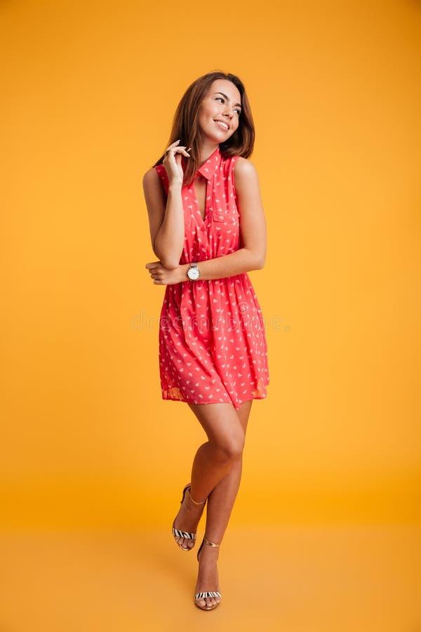 迷人的女孩全长画象红色礼服touchin的 库存照片