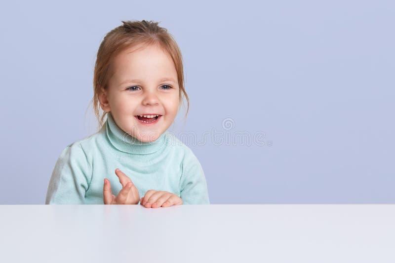 迷人的女孩接近的画象坐和嘲笑白色书桌的蓝色套头衫的,有愉快的表情, 免版税图库摄影