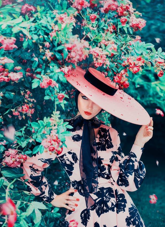 迷人的女孩掩藏一部分的她的面孔在有丝带的宽充满的桃红色帽子下 免版税库存照片