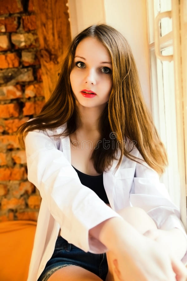 迷人的女孩画象衬衣的坐窗台 免版税库存照片