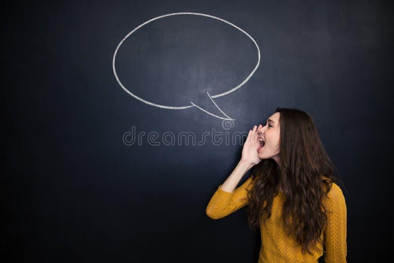 迷人的妇女尖叫反对黑板背景有讲话泡影的 库存照片