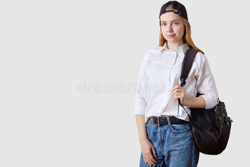 迷人的学生女孩室内射击,摆在对白色演播室墙壁,穿戴的丝毫衬衣,牛仔裤,遮阳盖帽,直接地看 免版税库存照片