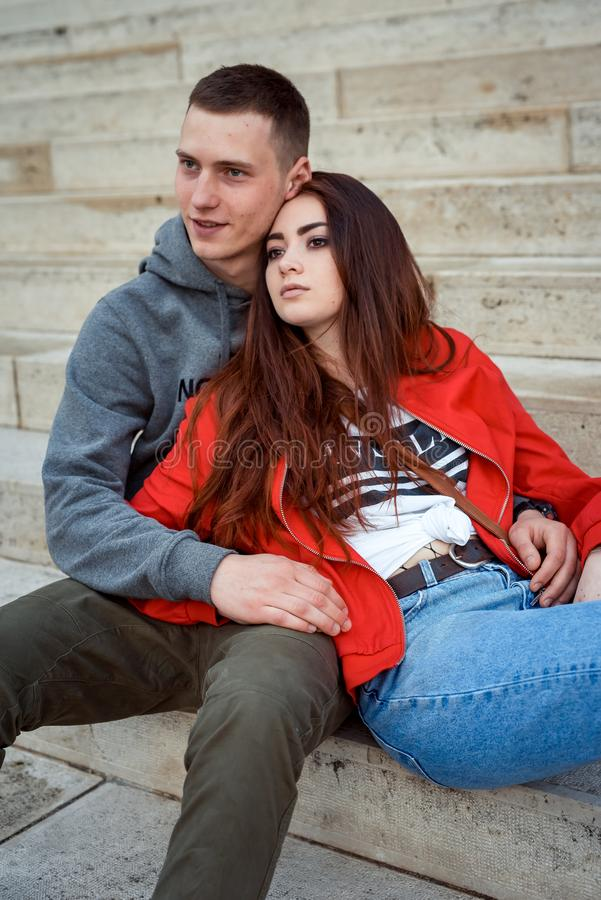迷人的年轻夫妇的特写镜头画象在爱的握手和坐台阶老历史 免版税图库摄影