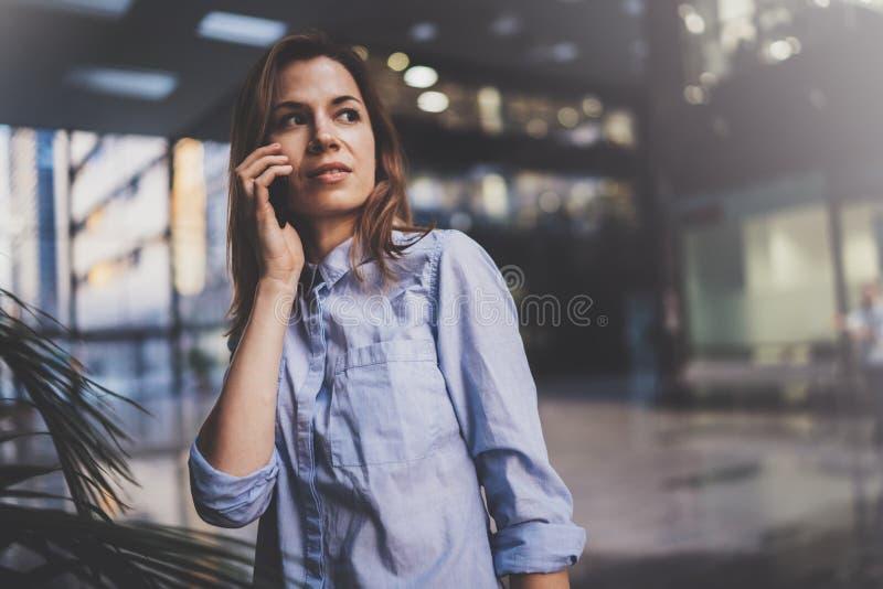 迷人的年轻女商人谈话与伙伴通过手机,当站立在现代商业中心时 免版税库存图片
