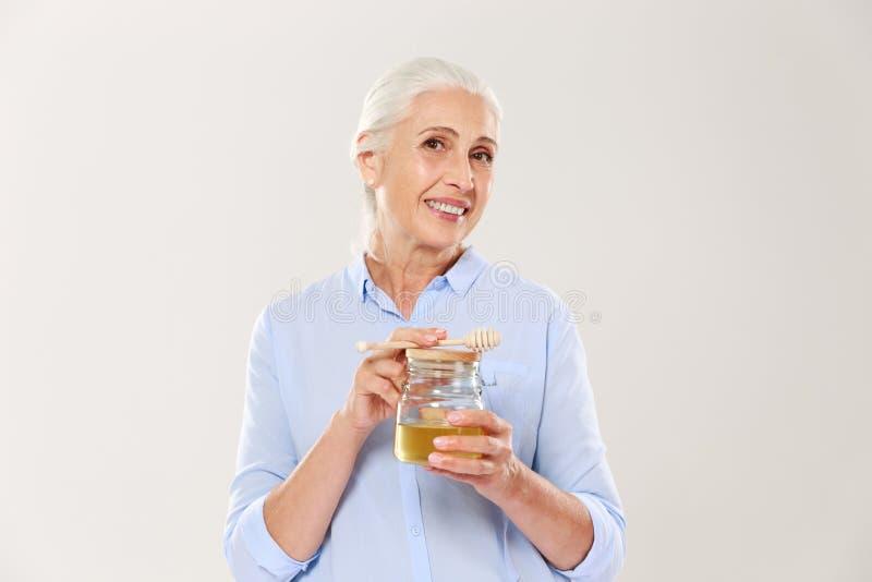 迷人的成熟妇女特写镜头画象,拿着蜂蜜瓶子wi 免版税图库摄影