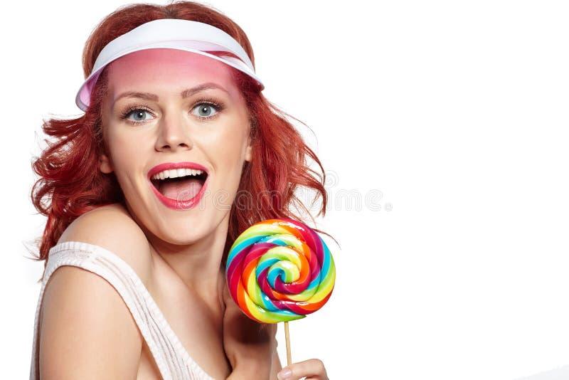 迷人的拿着棒棒糖的女孩佩带的帽子 免版税库存图片