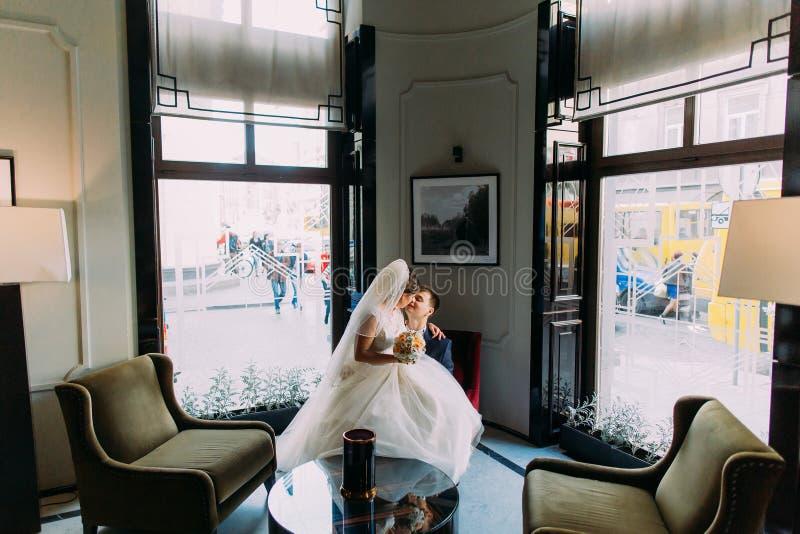 迷人的新娘坐她豪华内部的可爱的新郎膝盖与发光的窗口作为背景 免版税库存照片