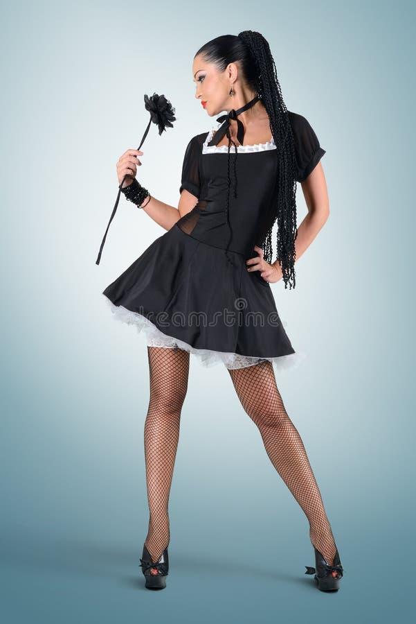 迷人的有黑色玫瑰的pinup时髦的佣人 库存照片