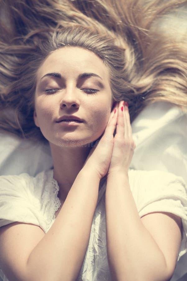 迷人的浪漫软的女孩美丽的年轻白肤金发的妇女取暖的太阳特写镜头画象在床上 图库摄影