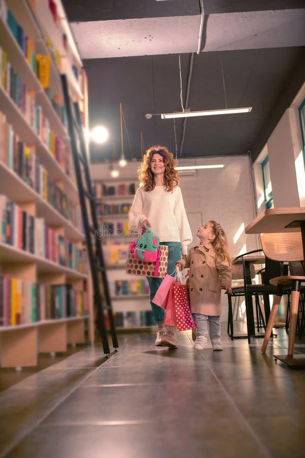 迷人的白肤金发的女孩谈话与她的母亲 免版税库存照片