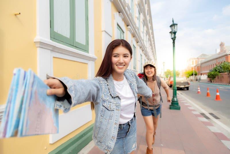 迷人的美女或旅客妇女扯拽她的朋友并且一起跑到一些旅游景点或有趣 免版税库存照片