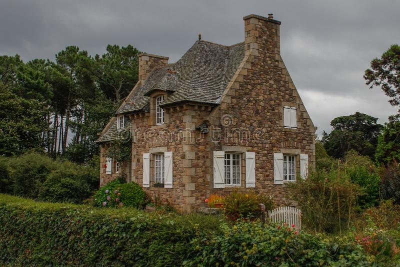 迷人的美妙的中世纪乡间别墅在有一个高屋顶和窗口的乡下与有一个绿色庭院的白色快门和 免版税库存照片
