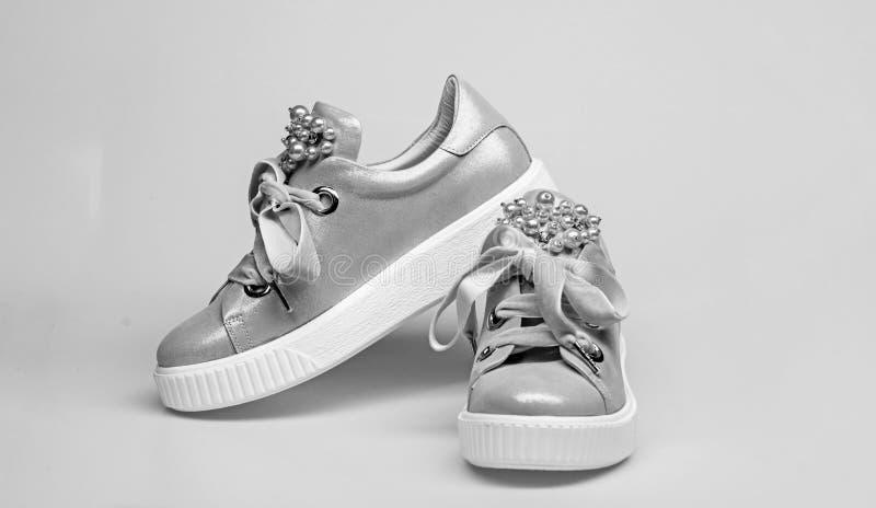 迷人的运动鞋概念 用珍珠和妇女的鞋类装饰的女孩成串珠状 在白色背景的逗人喜爱的鞋子 免版税库存图片
