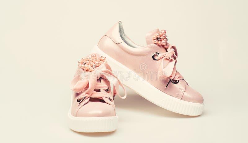 迷人的运动鞋概念 用珍珠和妇女的鞋类装饰的女孩成串珠状 在白色背景的逗人喜爱的鞋子 库存图片