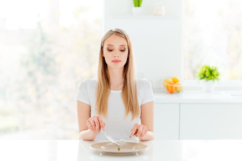迷人的逗人喜爱的青年千福年的被聚焦的美好的有动机的感受n膳食大盘刀子叉子画象坐桌穿戴 免版税库存图片