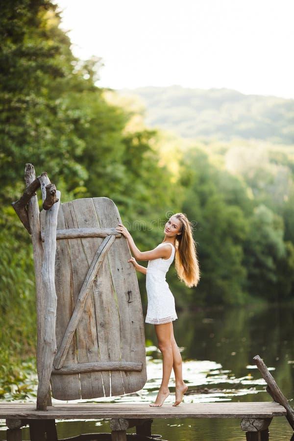 迷人的长发深色的在白色礼服步行的女孩有吸引力的模型由河 情感大气画象 免版税库存图片