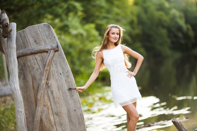 迷人的长发深色的在白色礼服步行的女孩有吸引力的模型由河 情感大气画象 库存照片