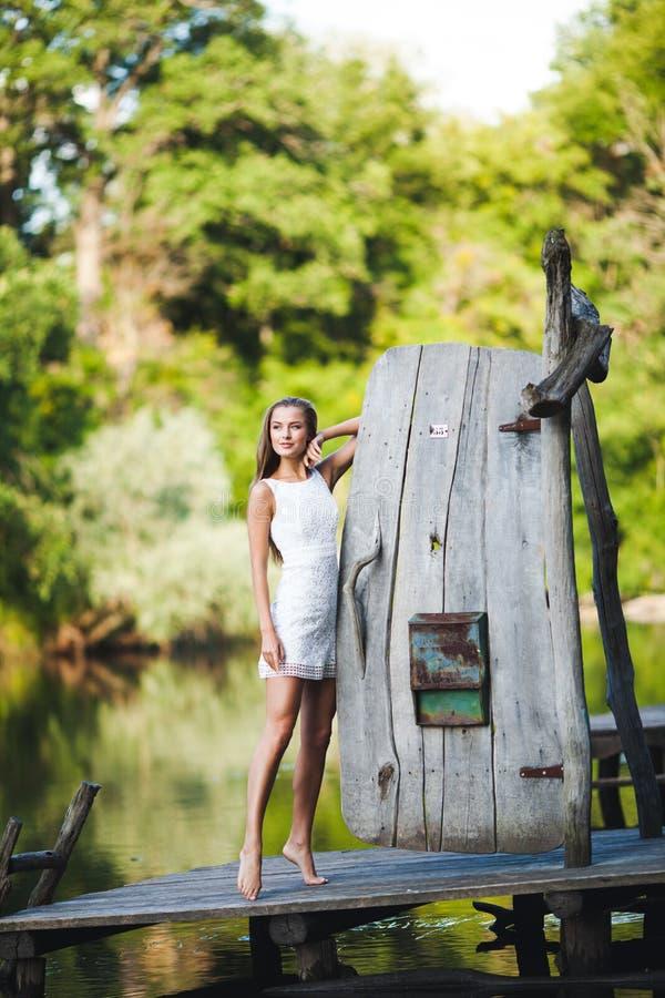迷人的长发深色的在白色礼服步行的女孩有吸引力的模型由河 情感大气画象 免版税图库摄影