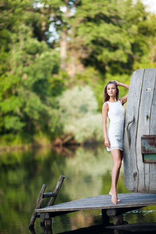 迷人的长发深色的在白色礼服步行的女孩有吸引力的模型由河 情感大气画象 库存图片