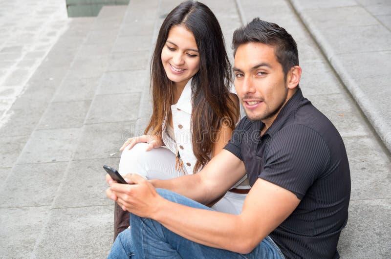 迷人的年轻夫妇坐大厦跨步使用手机和愉快互动,都市旅游概念 免版税库存照片
