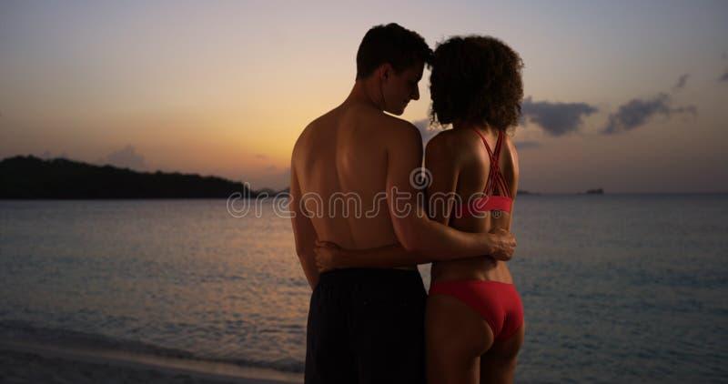 迷人的从海滩的混合的族种夫妇观看的日落 免版税图库摄影