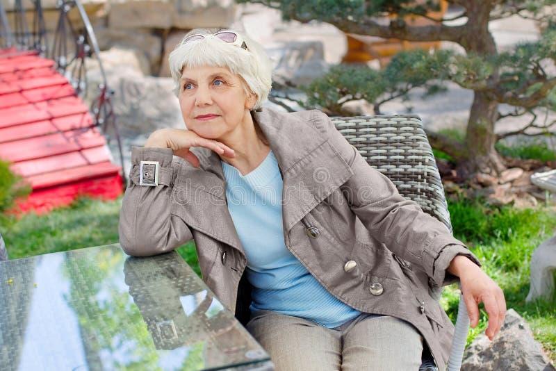 迷人的年长灰发的妇女放松的坐在庭院里 免版税图库摄影