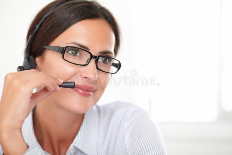 迷人的年轻雇员交谈在耳机 免版税图库摄影