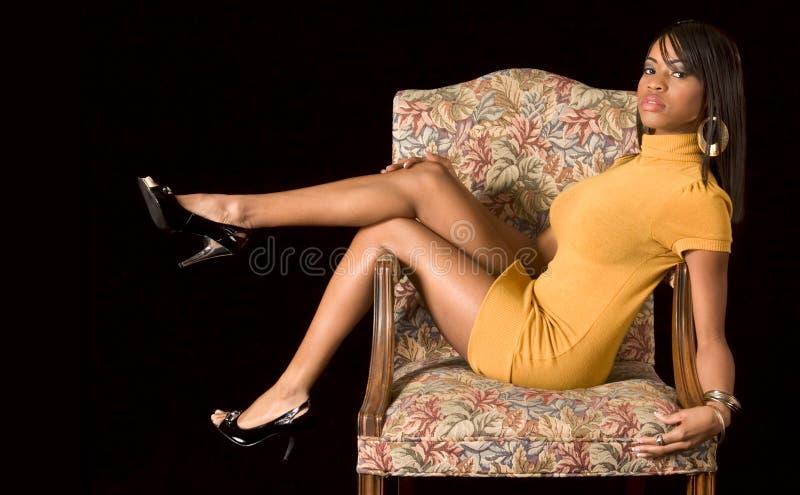迷人非洲裔美国人的椅子的女孩 免版税库存照片