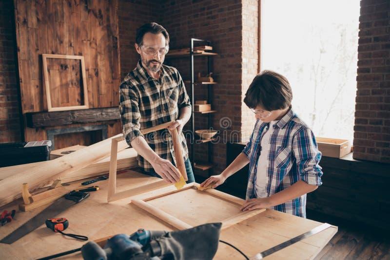 迷住好的俏丽的可爱的爸爸儿子工匠学徒用途用户设备硬木职业工作场所穿戴的画象 图库摄影