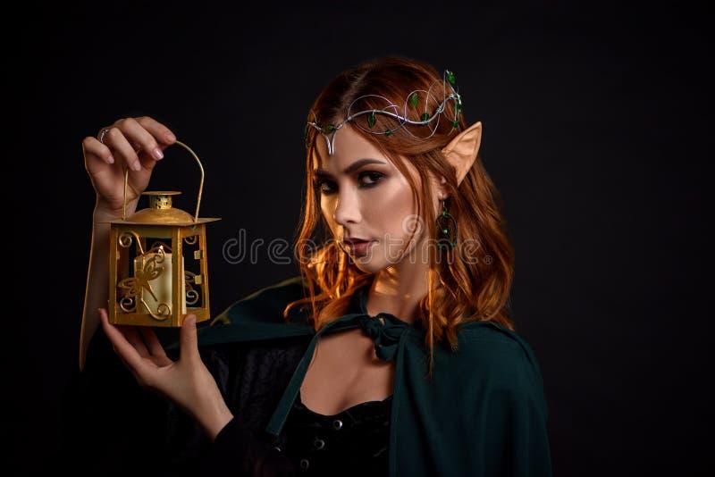 迷住有红色头发的神秘的女孩画象在斗篷 库存照片