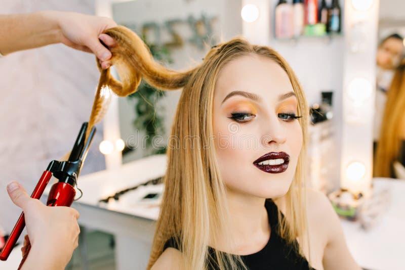 迷住白肤金发的妇女的特写镜头画象准备对庆祝,在发廊的党 时髦的构成,做发型 免版税库存照片