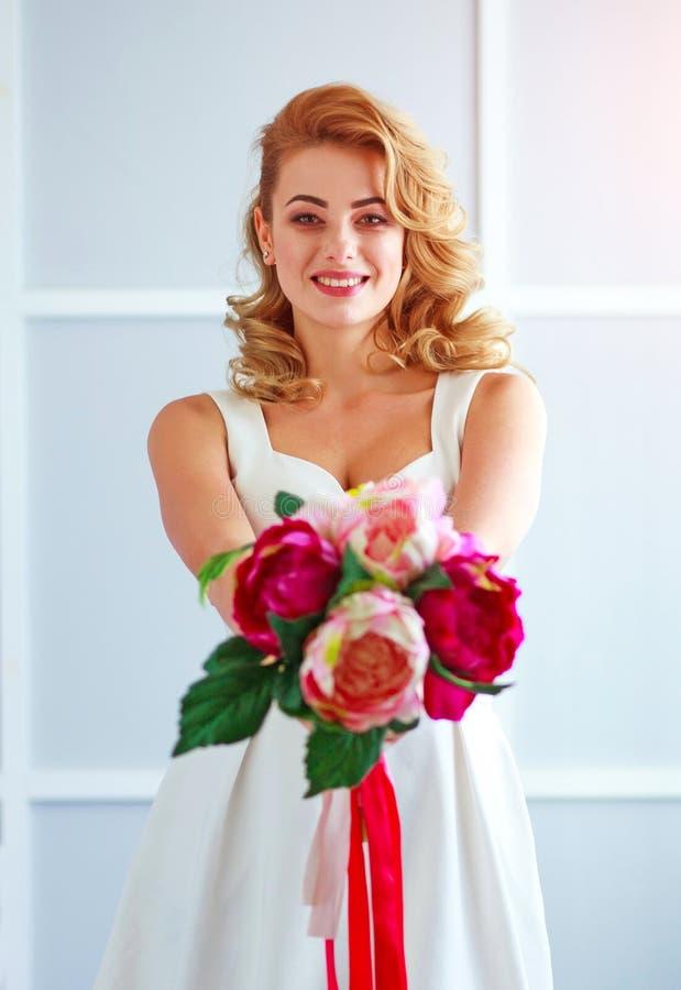 迷住白色礼服的愉快和快乐的年轻女人新娘有花束的在演播室 图库摄影
