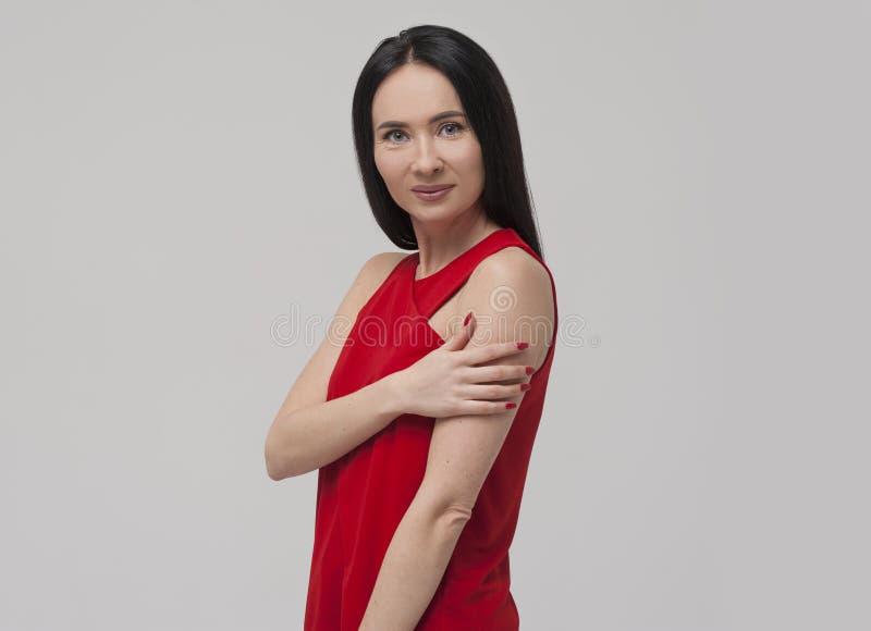 迷住穿红色女衬衫的年轻深色的妇女画象  图库摄影