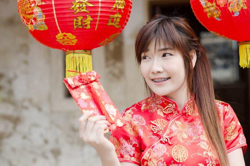 迷住美丽的亚洲女服cheongsam礼服的画象从她的家庭得到红色信封 俏丽的女孩显示红色信封 免版税库存图片