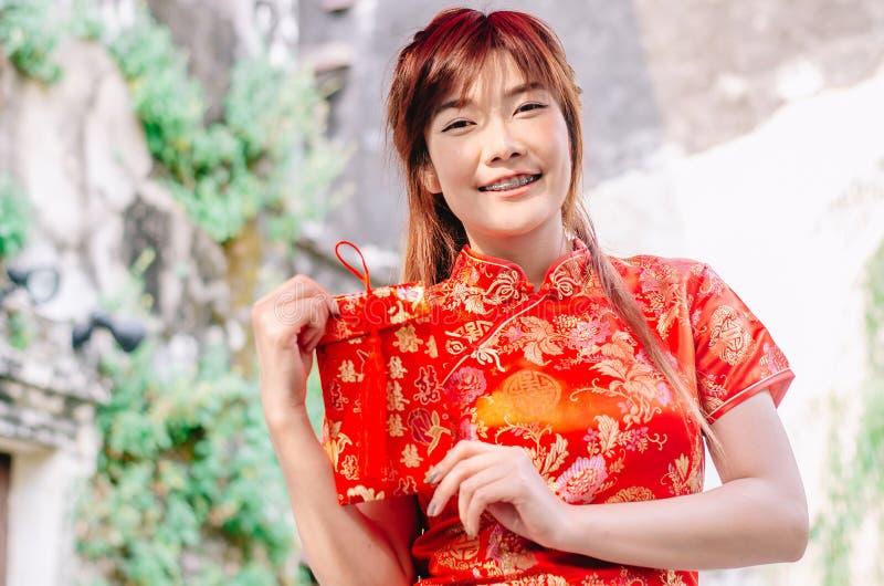 迷住美丽的亚洲女服cheongsam礼服的画象从她的家庭得到红色信封 俏丽的女孩显示红色信封 库存图片