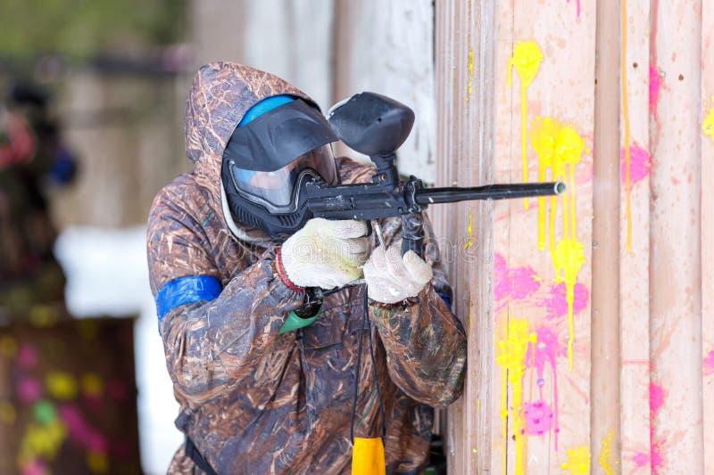迷彩漆弹运动比赛在冬天 在设防后的凉快的射击者 免版税库存图片