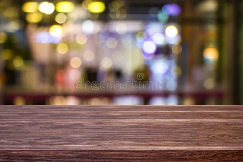 迷离咖啡馆餐馆或咖啡馆空黑暗的木桌有蒙太奇产品的被弄脏的轻的金bokeh抽象背景 免版税库存图片