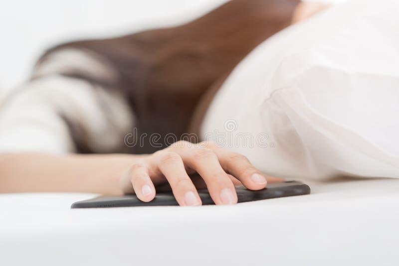 迷离妇女通过智能手机闹钟和转动打瞌睡电话闹钟醒了 免版税库存图片