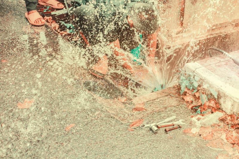 迷离水管工运作的修理破裂的导管和替换在孔用水行动在路旁 免版税图库摄影