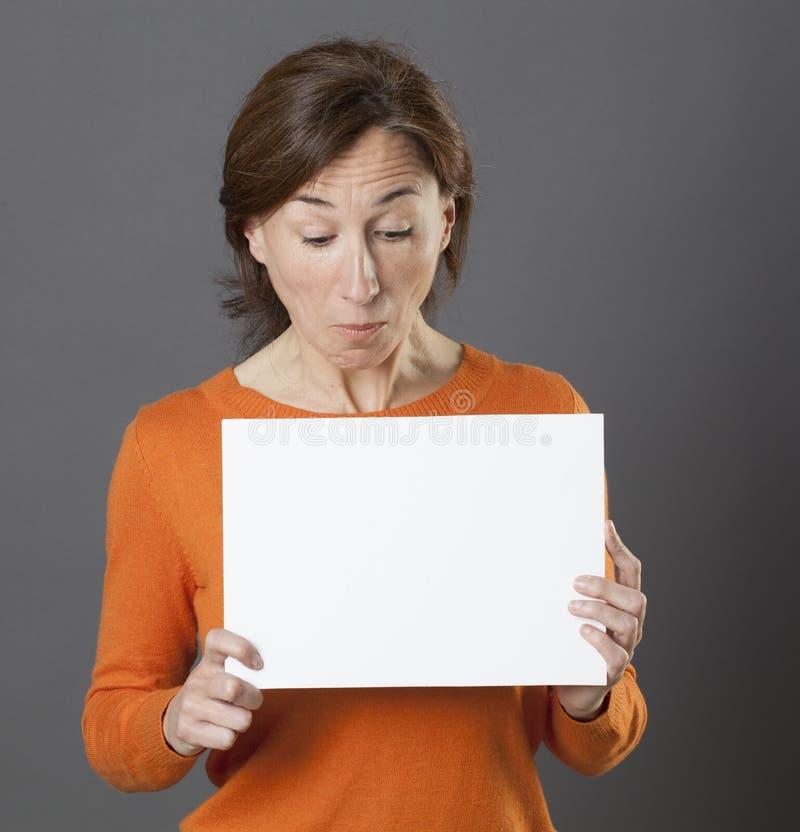 迷茫的中部变老了拿着白色通信盘区,灰色背景的妇女 库存图片