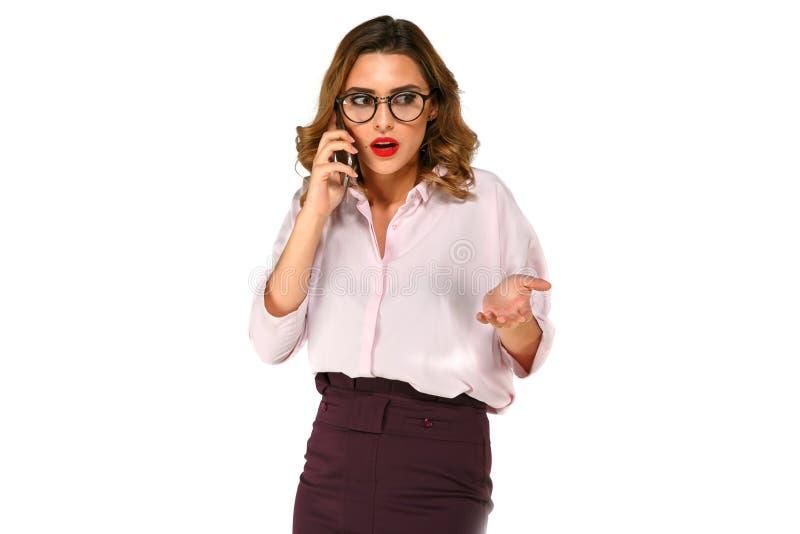 迷茫的女商人谈话在电话 免版税库存图片