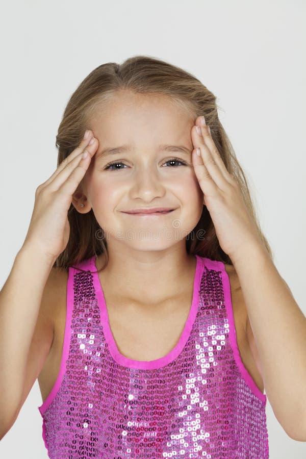 年轻迷茫的女孩画象用在头的手反对灰色背景 免版税图库摄影