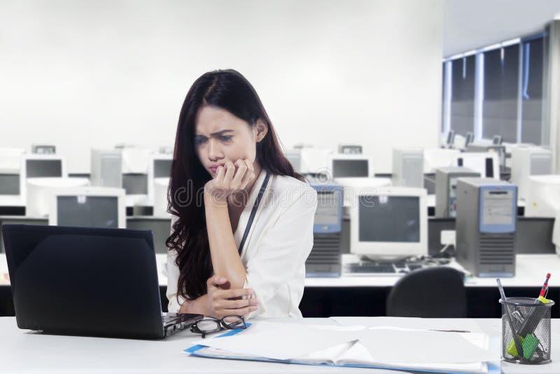 迷茫的女实业家与膝上型计算机一起使用 免版税库存照片