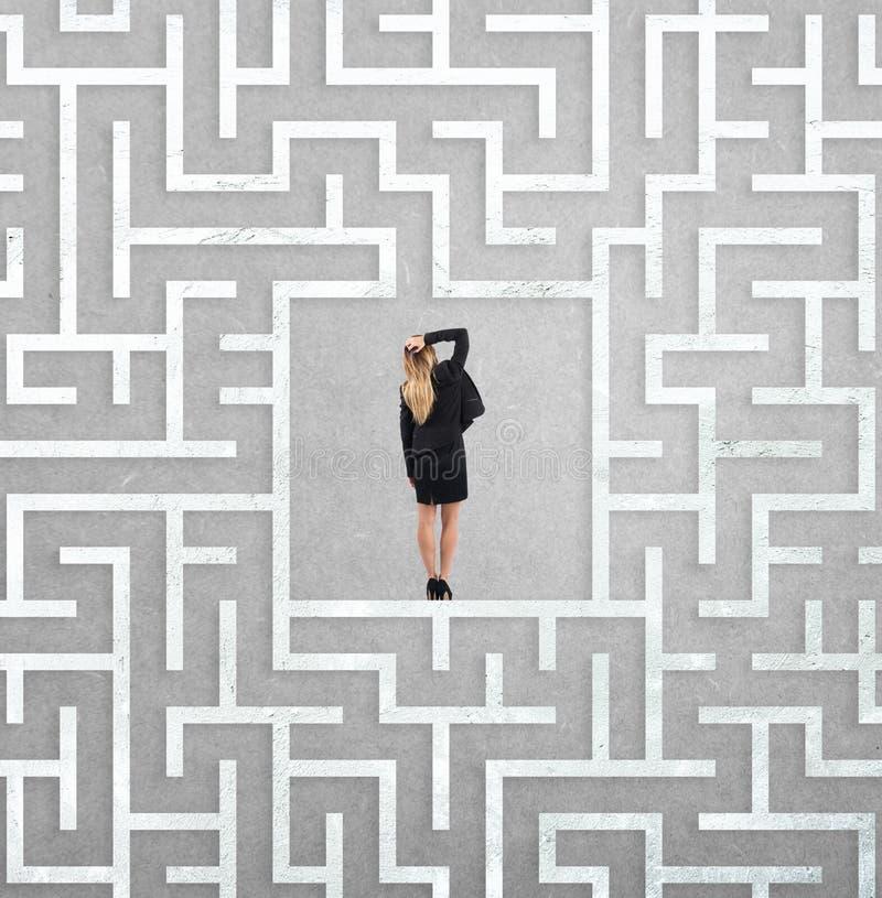 迷茫的女实业家在迷宫的中心 图库摄影