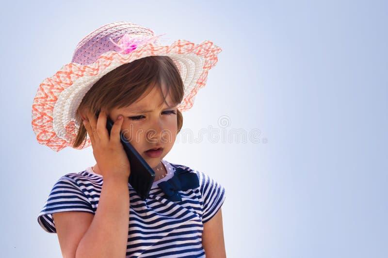 迷茫的小女孩谈话在手机智能手机, 免版税图库摄影